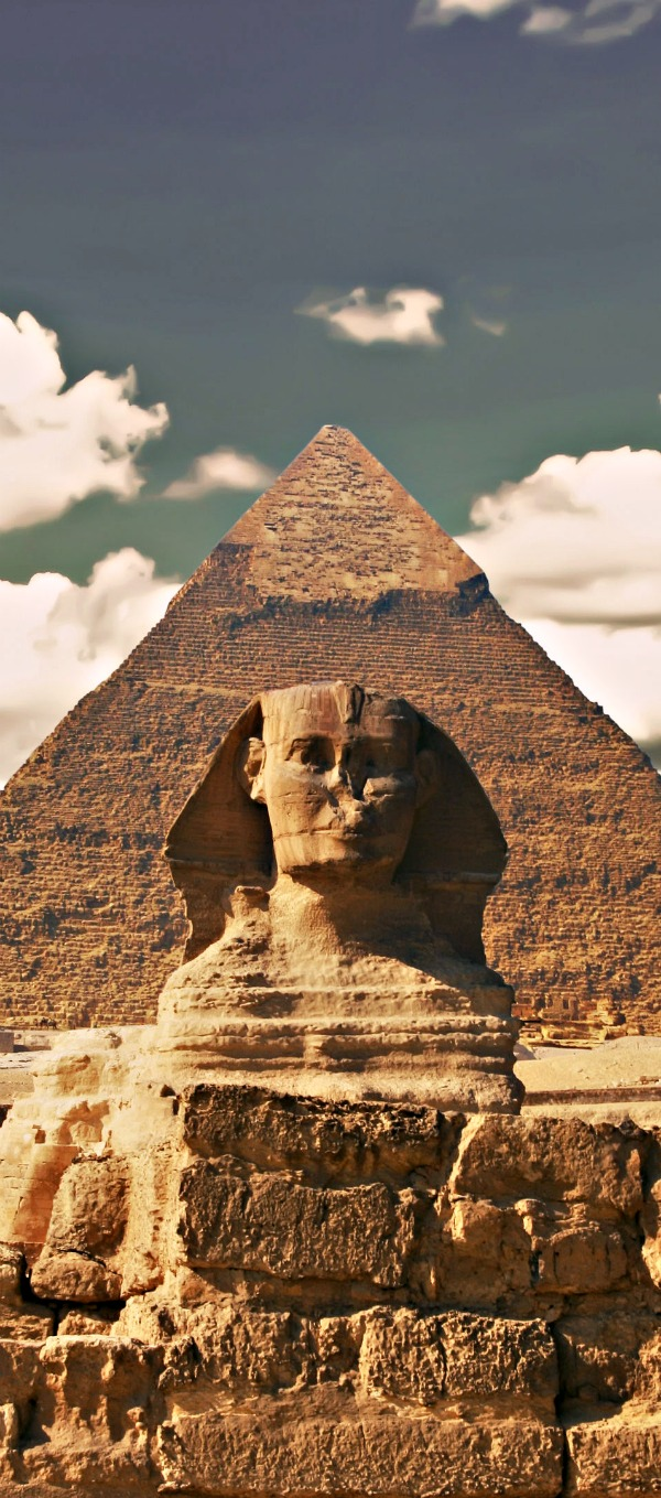 Great Sphinx including pyramids of Menkaure and Khafre in the background on a clear sunny, blue sky day in Giza, Cairo, Egypt